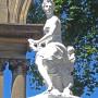 La staute représente Flore, une guirlande à la main devant un enfant ailé